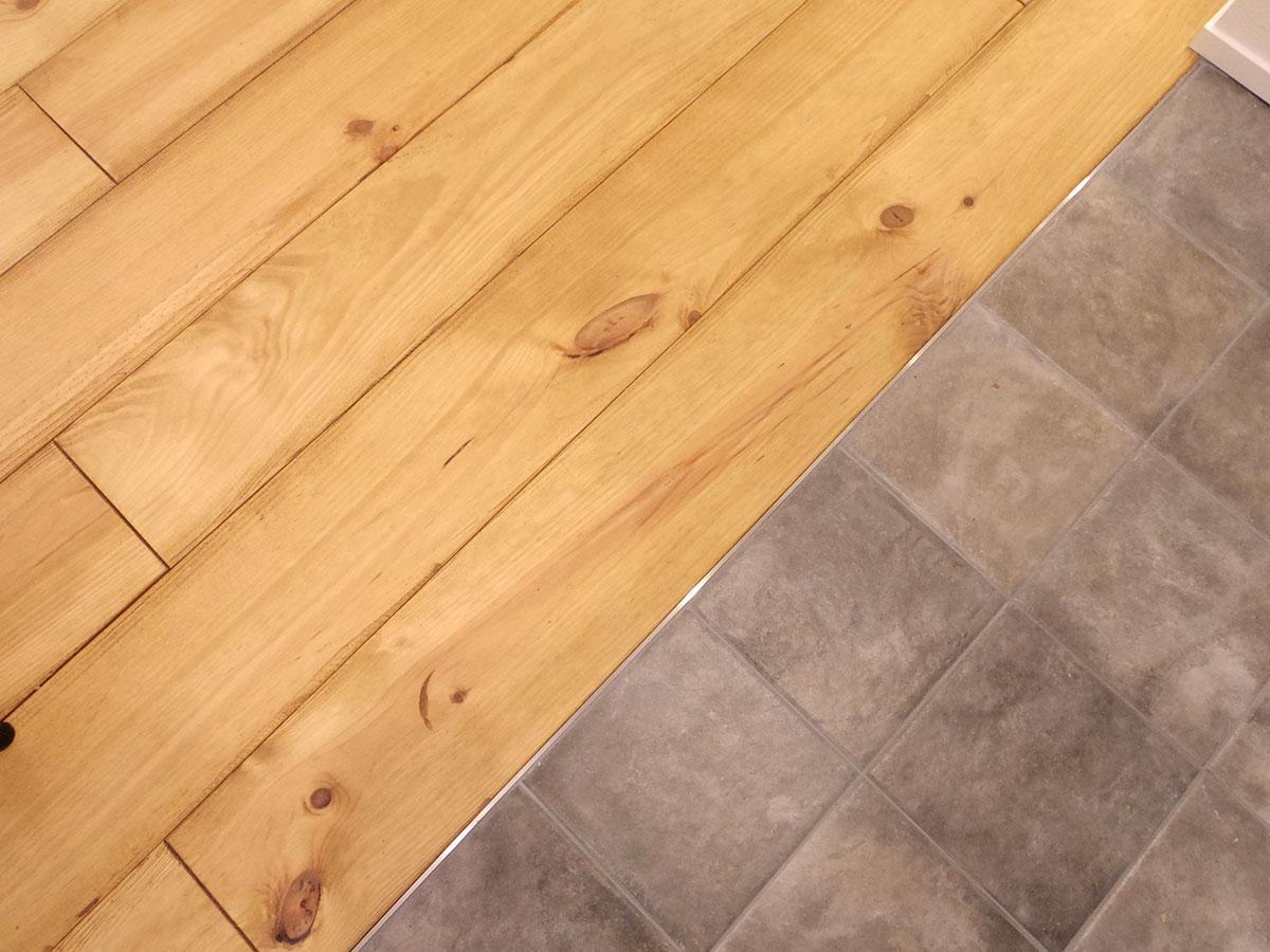 床材はアンティーク加工が施された無垢のパイン材。キッチン周りは防水タイル
