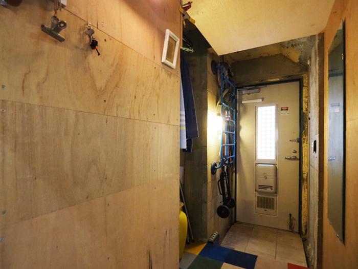 玄関。かなり大胆に仕上げを剥がし、合板やカーペットなどで一部を仕上げなおしている