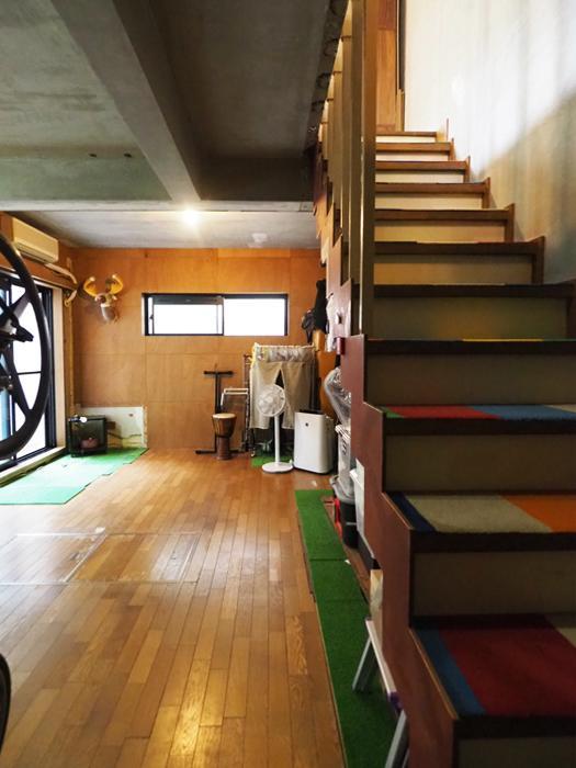 地下。階段と廊下の壁を剥がして広い空間にしている。グリーンのカーペットが敷かれているところは床の仕上げ材がない