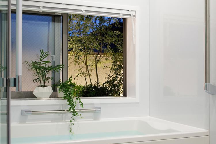浴室。大きな窓からバルコニーにある植物を眺められる