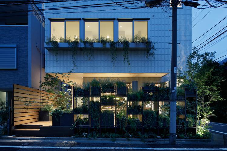 通りに面して植栽の棚が並ぶ。玄関とは別に左手のウッドデッキからアトリエに入ることもできる