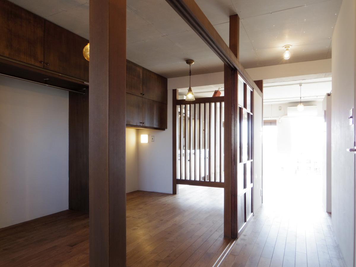 玄関側の土間スペースから見た寝室。窓からの光を取り込めるよう、リビングとの境はあえて格子状にしている