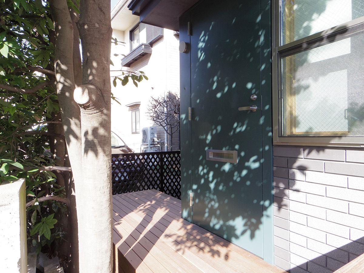 植栽の緑に守られるような玄関。デッキには自転車や植物を置くことも可能