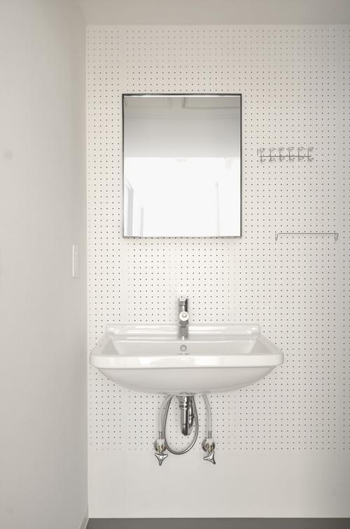洗面の壁も有孔ボード仕様。鏡もかけてあるものなので、好みのものにかえることもできる