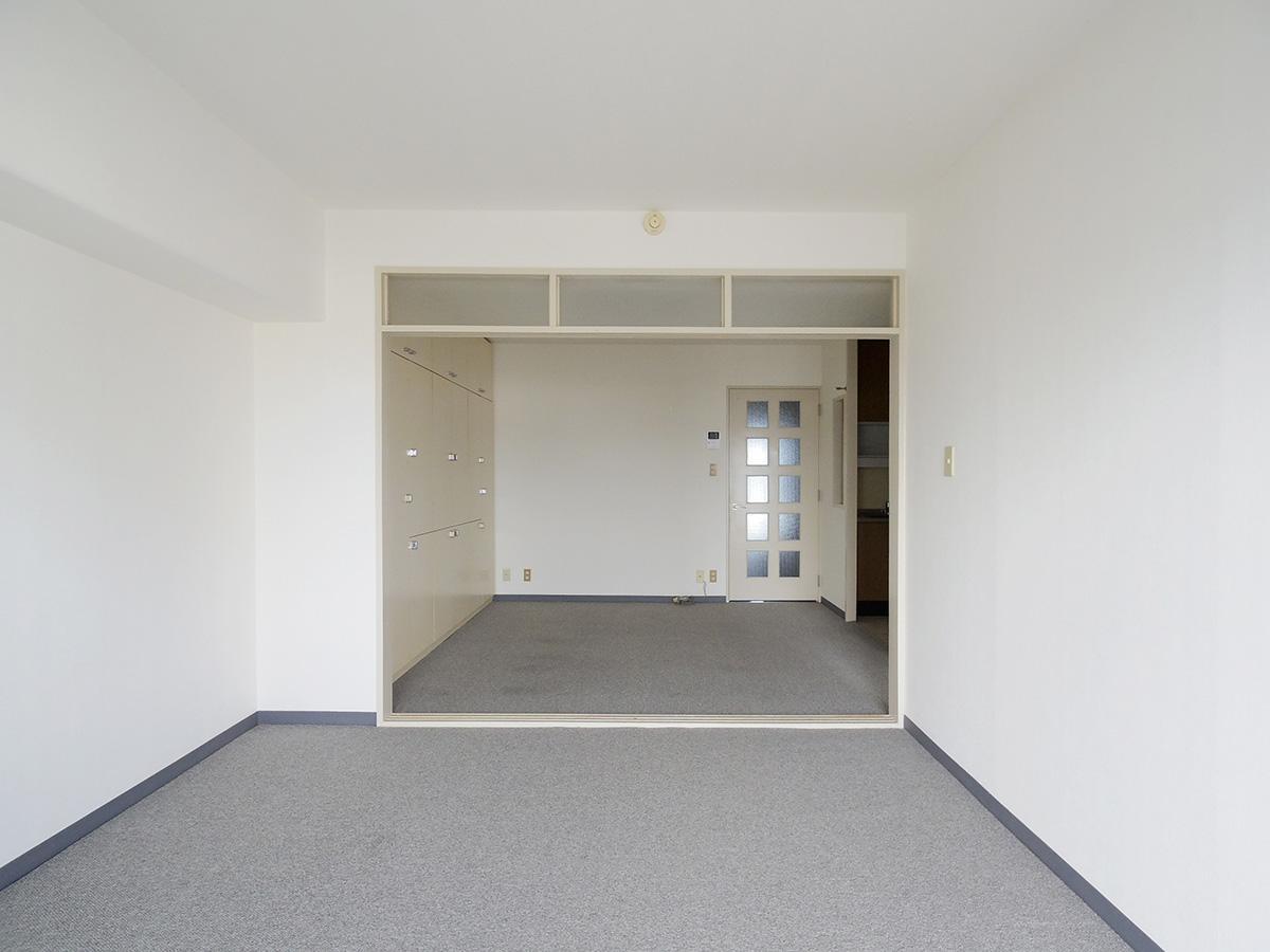 グレーのカーペットと白い壁紙のシンプルな内装