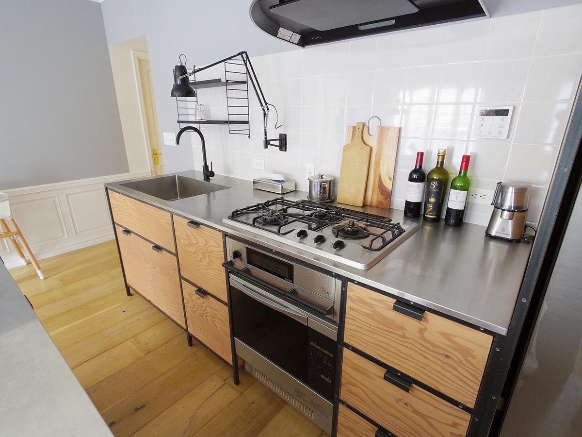 キッチンの壁は白いタイル張り。黒いメタルフレームと組み合わせた合板がいい雰囲気