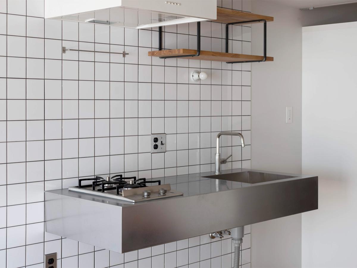 ミニマルなキッチン。床から天井まで一面タイル張り