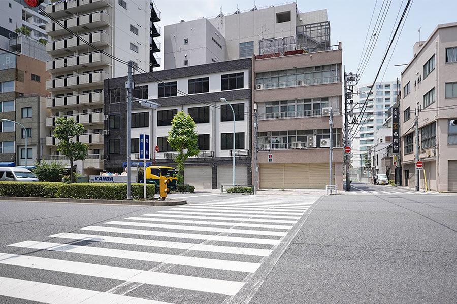 真ん中の白と濃紺の外観が特徴のビル。交差点のすぐそばにあります
