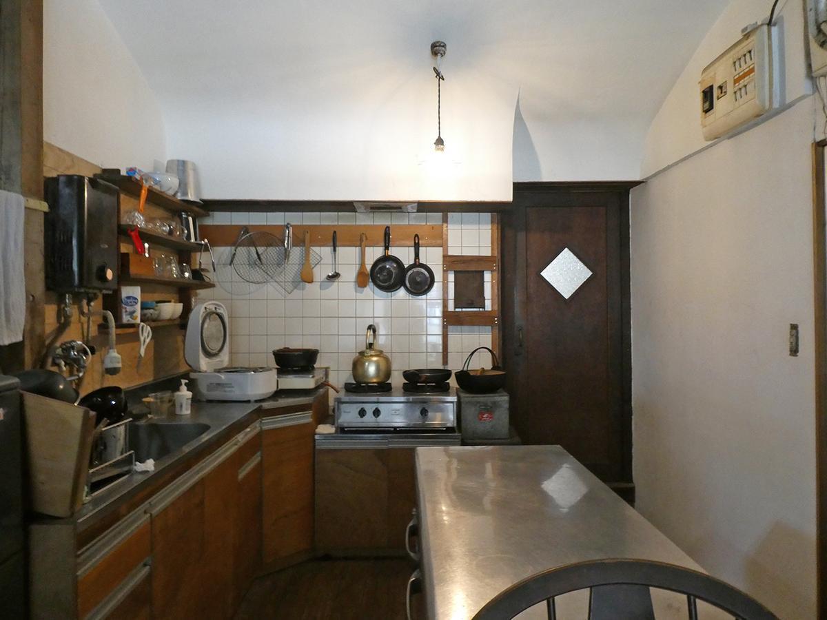 キッチン。ぶら下がった裸電球や木のドアの雰囲気がいい