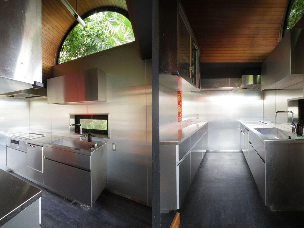 半円の窓から緑地の緑を映し込む使いやすそうなキッチン
