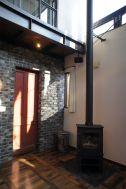 O'gu bijou/個人宅 (オッグビジュー):1階 赤い扉と薪ストーブ
