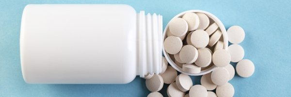 Container with pills close-up on a blue background