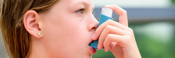 Girl uses an inhaler during an asthma attack, close-up