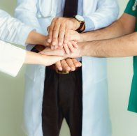 Close up portrait of doctors teamwork stacking hands together at