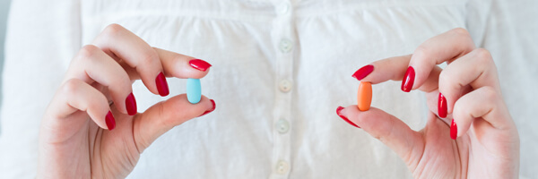 woman holding red blue pills medication treatment
