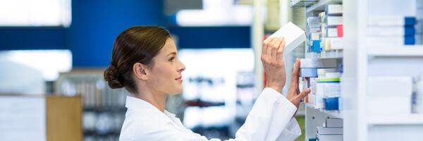 Pharmacist checking medicine in shelf at pharmacy