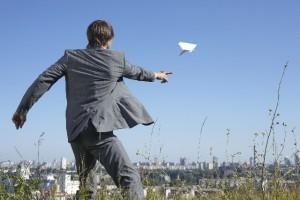 紙飛行機を飛ばす男性