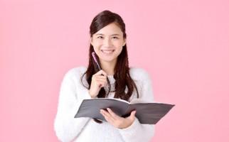 ノートを片手にニッコリする女性