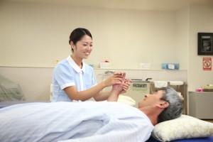 患者さんの手をにぎる女性