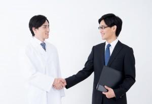白衣の男性とスーツの男性が握手