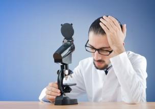 悩む白衣の男性と顕微鏡
