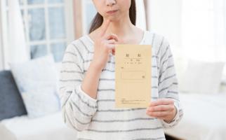 給与の封筒を持って悩む女性
