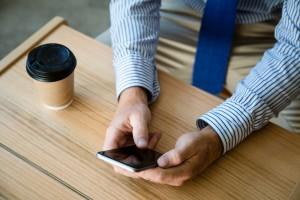 カフェでスマホを操作する男性