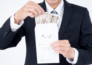 賞与と書かれた封筒の中のお金を確認する男性