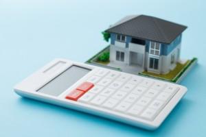 家の模型と電卓の写真