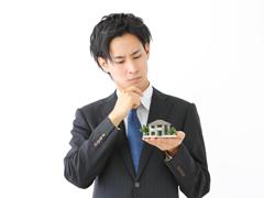 家を見て考える男性