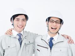 笑顔の作業着姿の男性たち