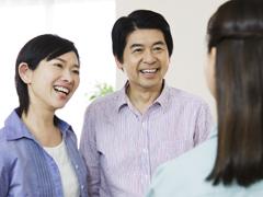 夫婦と談笑する作業着の女性