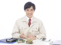 家の模型を笑顔で示す作業着男性