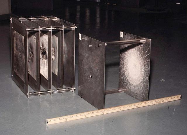 5枚重ねた金属板が4枚目まで貫通されてるのに 1枚目と5枚目の間隔と同じ幅だけ開けておいた2枚の金属板だったら2枚目で止まっている不思議な画像  ホイップルシールドといって高速で小型のデブリなら分厚い金属より何もない隙間のほうが効果的 一種の空間装甲だな