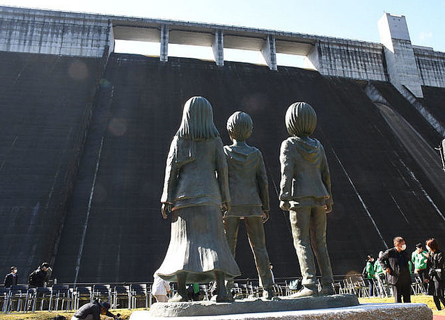 高さ94mのダムを作中の壁に見立て、3人が見上げる姿になっている