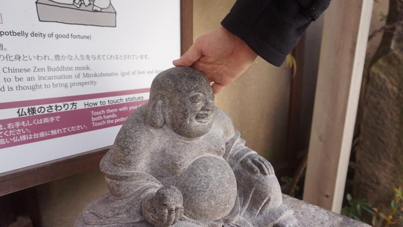 Touch a Buddha statue