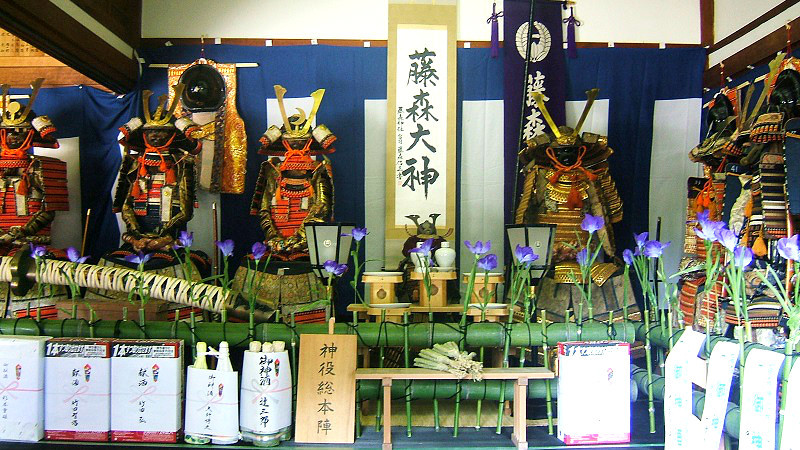 """A """"Shinkosai"""" procession with people wearing samurai armor and helmets, and carrying portable shrines"""