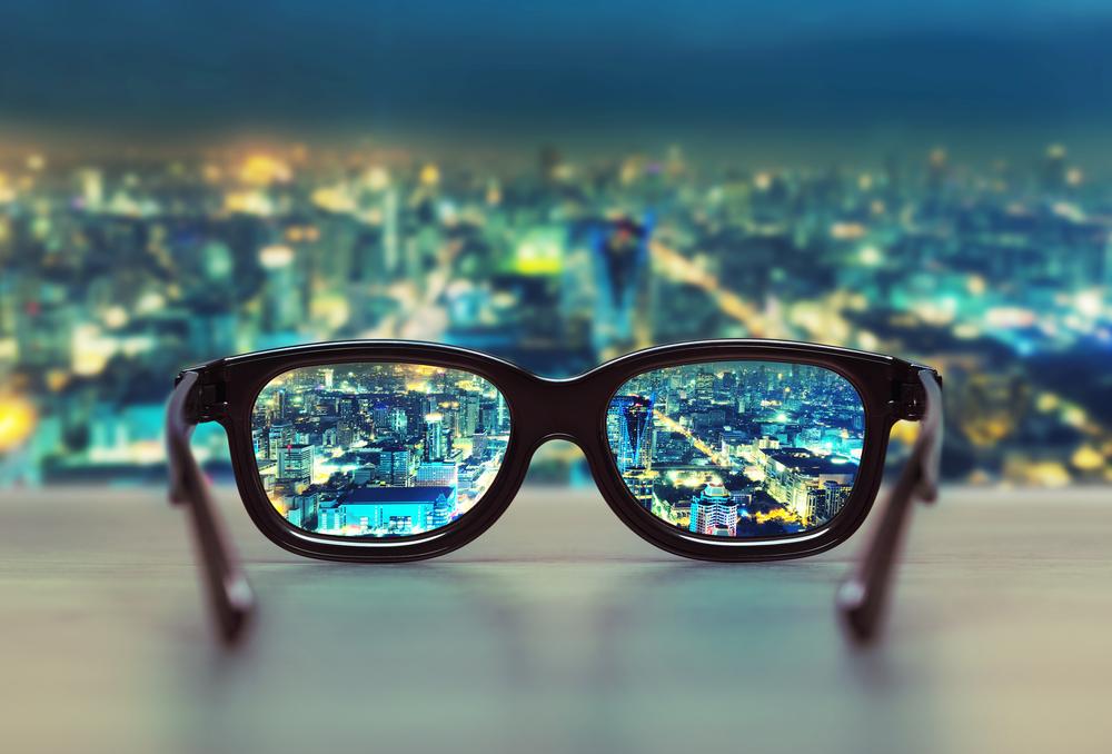 夜景の見えるデスクに置かれたメガネ
