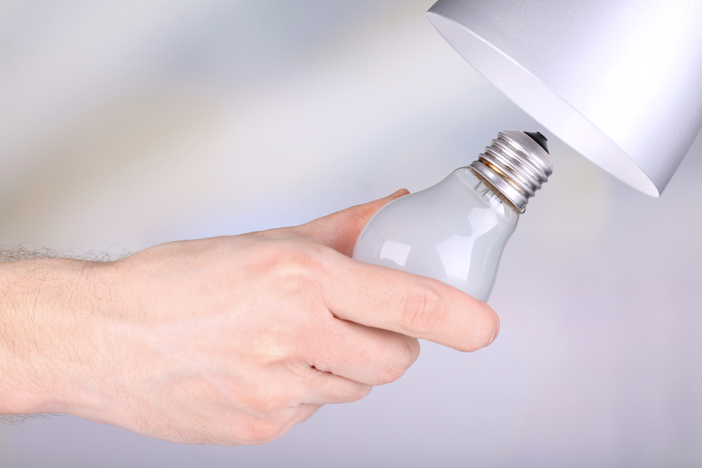 電球を交換している女性の手元