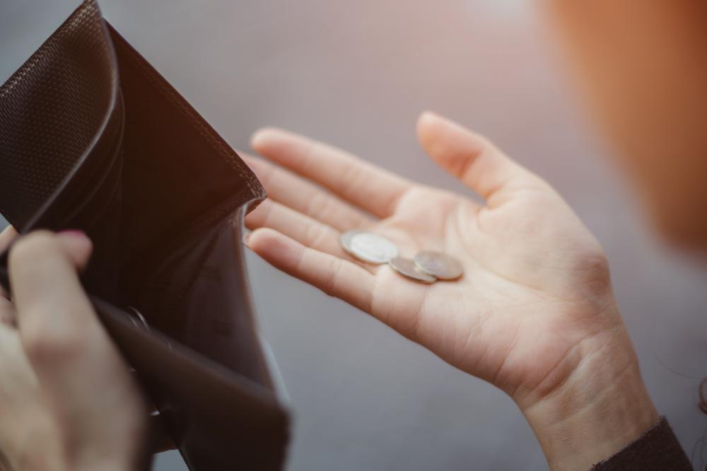 手のひらに並べた硬貨を見ている男性