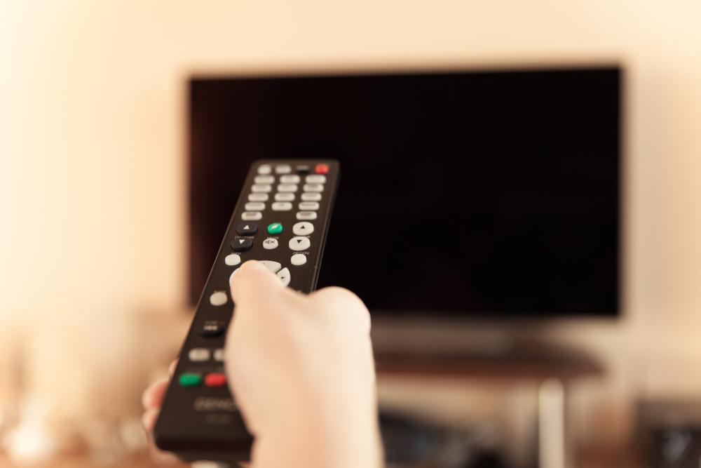 テレビのリモコンを持つ手