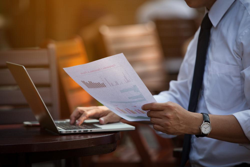 紙に書かれたデータを読む男性