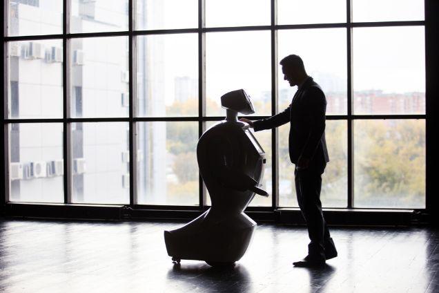 オフィスで向かい合って立つ人間とロボット