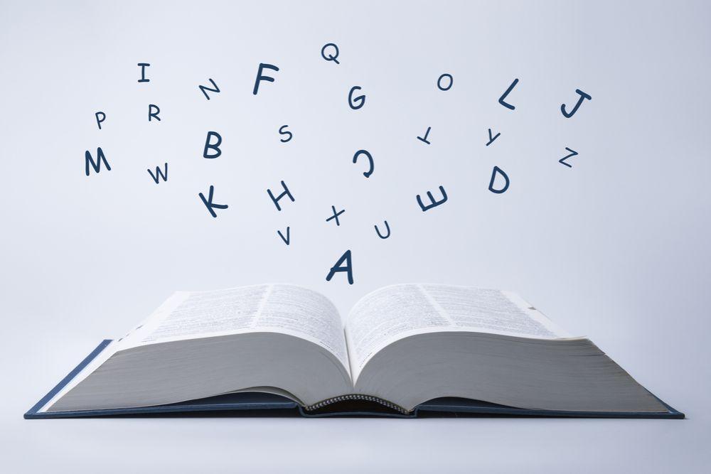 本の見開きからアルファベットが飛び出す様子