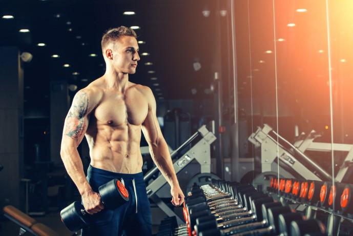 ダンベルサイドベントで体幹を鍛えている男性