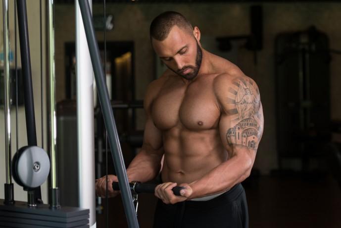 ケーブルカールで体を鍛えている男