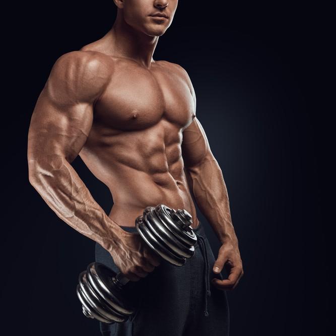 正しい呼吸法でダンベルサイド弁とトレーニングをしている男
