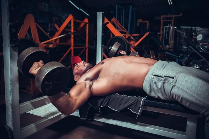 デクラインダンベルプレスで大胸筋を伸張させている男