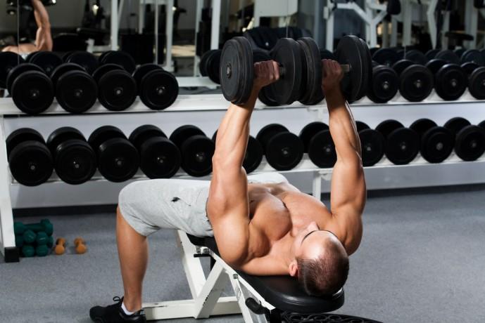 デクラインダンベルプレストレーニングで大胸筋を収縮させている男性