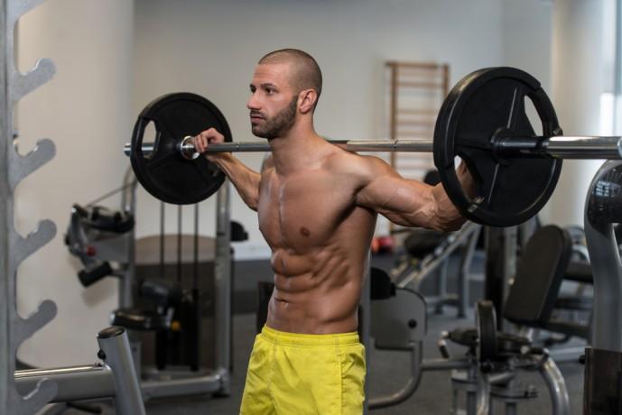 バーベルカーフレイズでふくらはぎを鍛える男性